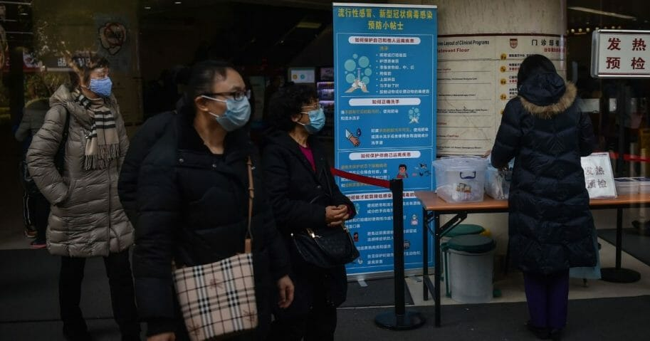 People walk next to signage detailing hygenic practices to prevent the spread of a SARS-like coronavirus at the Huashan Hospital in Shanghai on Jan. 21, 2020.