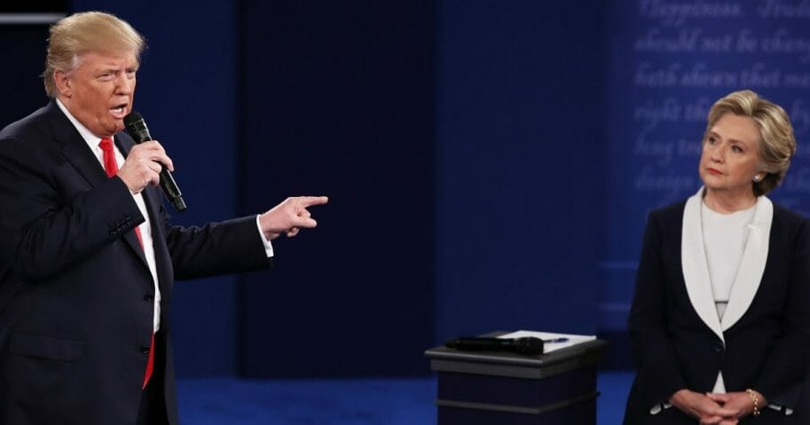 Donald Trump gestures toward Hillary Clinton listens during their presidential town hall debate at Washington University in St. Louis on Oct. 9, 2016