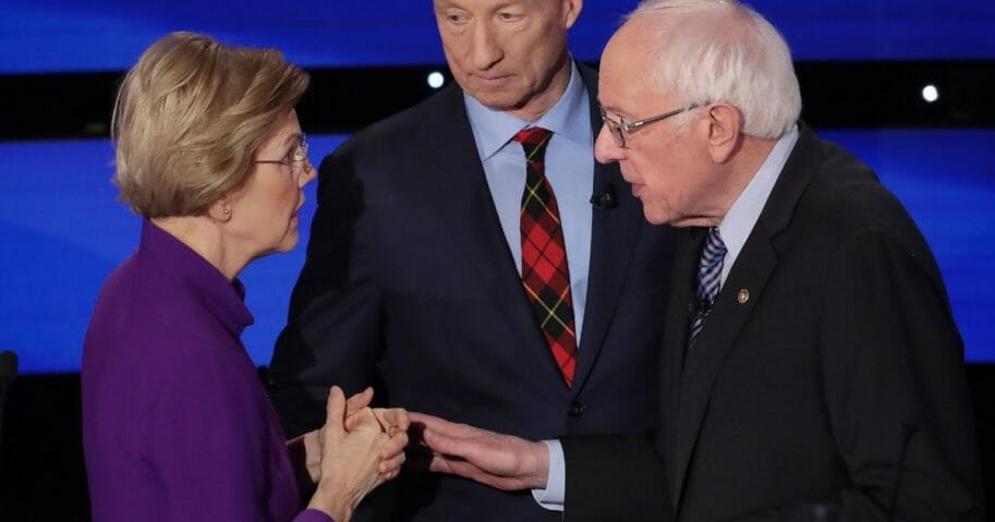 Sen. Elizabeth Warren (D-Massachusetts) and Sen. Bernie Sanders (I-Vermont) speak as Tom Steyer looks on after the Democratic presidential primary debate at Drake University on Jan. 14, 2020, in Des Moines, Iowa.