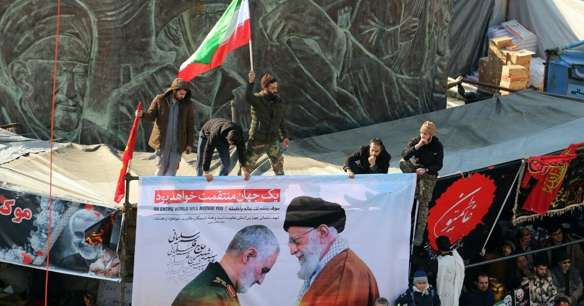 Iranians carry a picture of Supreme Leader Ayatollah Ali Khamenei, right, giving a medal to Gen. Qassem Soleimani during the latter's funeral procession in Tehran on Jan. 6, 2020.