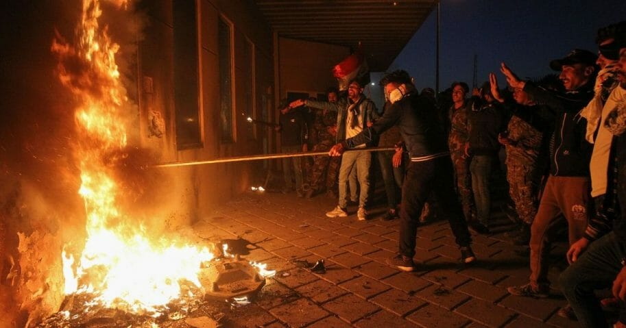 Members of Iraq's Hashed al-Shaabi military network set a door ablaze as they try to break into the U.S. embassy building in Baghdad on Dec. 31, 2019, during a rally to vent anger over weekend air strikes that killed pro-Iran fighters in western Iraq.