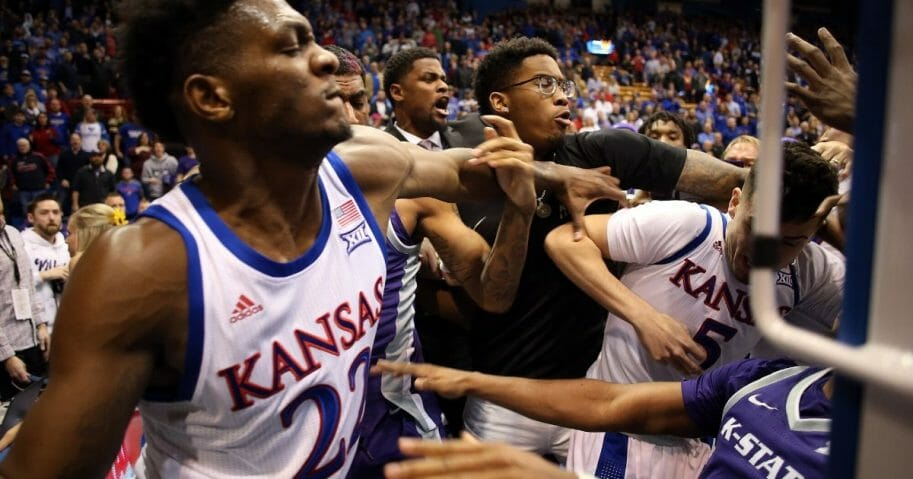 James Love III of the Kansas State Wildcats grabs Elijah Elliott (No. 5) of the Kansas Jayhawks and Silvio De Sousa (No. 22) during a brawl after the game at Allen Fieldhouse in Lawrence, Kansas, on Jan. 21, 2020