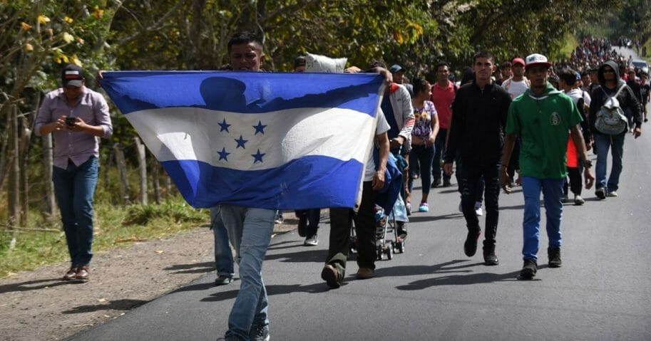 Honduran migrants walk with a Honduran flag near Esquipulas, Chiquimula department, Guatemala, on Jan. 16, 2020, after crossing the border in Agua Caliente from Honduras on their way to the U.S.
