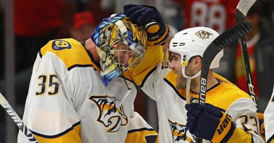 Pekka Rinne of the Nashville Predators celebrates a win against the Chicago Blackhawks and his first career goal, an empty net shot, with Rocco Grimaldi at the United Center in Chicago on Jan. 9, 2020. The Predators defeated the Blackhawks 5-2.