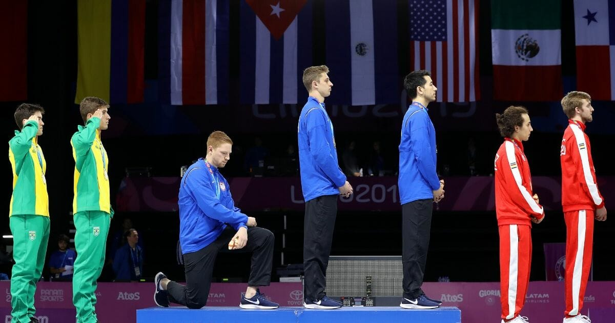 Gold medalist Race Imboden of the United States takes a knee during the national anthem ceremony on the podium of fencing men's foil team gold medal match match on day 14 of Lima 2019 Pan American Games at Fencing Pavilion of Lima Convention Center on Aug. 9, 2019, in Lima, Peru.