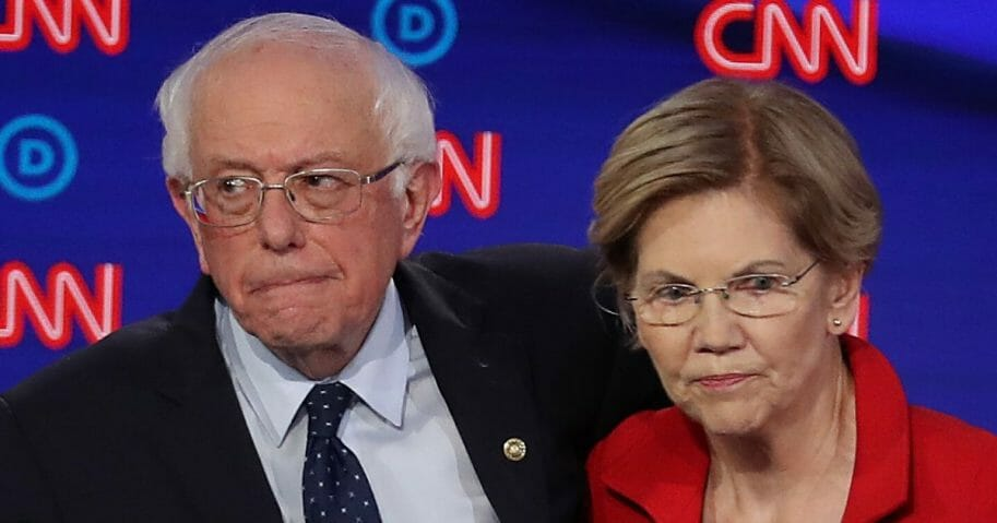 Democratic presidential candidates Sen. Bernie Sanders and Sen. Elizabeth Warren stand together after a primary debate at the Fox Theatre in Detroit on July 30, 2019.