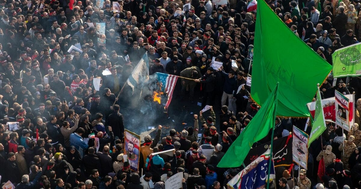 Mourners burn U.S. and Israeli flags during a funeral ceremony for Iranian Major General Qassem Soleimani and others who were killed in Iraq by a U.S. drone strike on Jan. 6, 2020, in Tehran, Iran.
