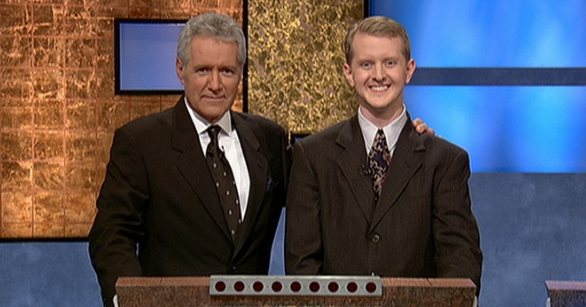 """""""Jeopardy!"""" host Alex Trebek poses with contestant Ken Jennings in 2004 after Jennings' earnings from his record-breaking streak on the game show surpassed $1 million."""