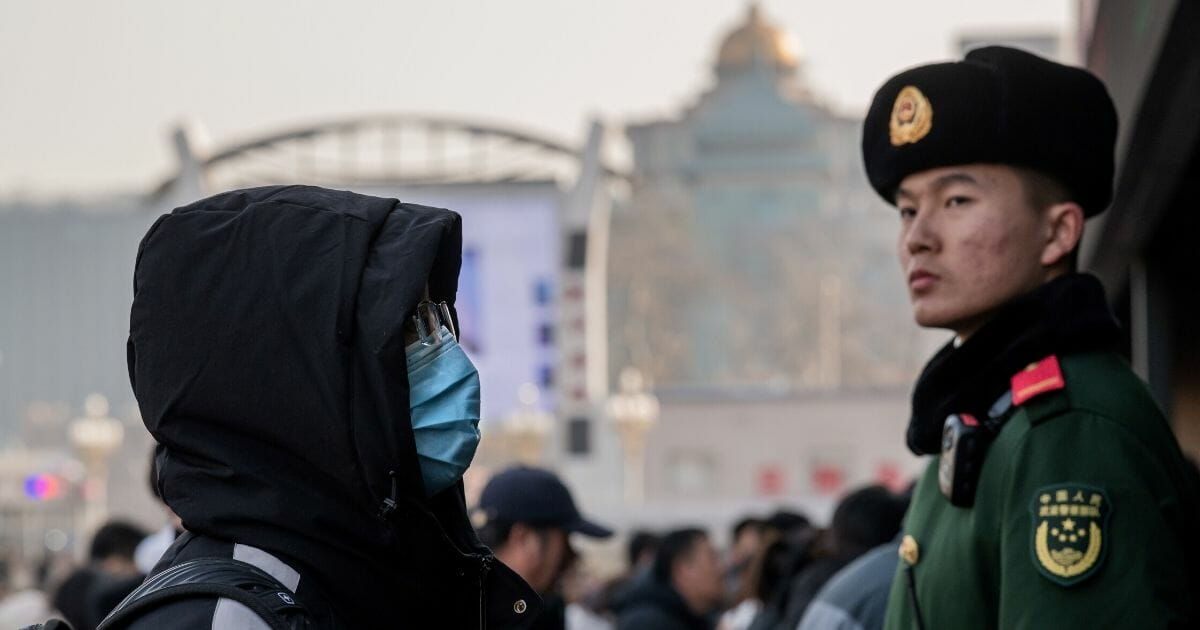 A man wearing a protective mask passes a guard in Beijing.