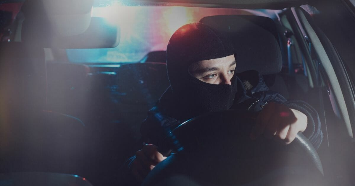 A driver sits at a traffic stop with his face obscured.