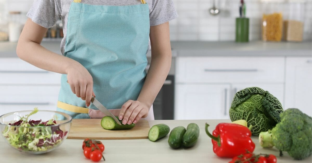 Stock image of a woman in an apron cooking in a kitchen.