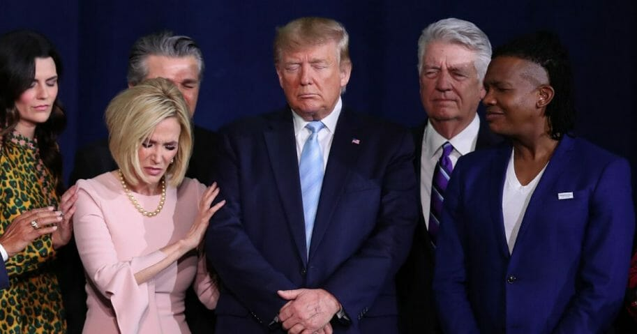 "Faith leaders pray over President Donald Trump during an ""Evangelicals for Trump"" campaign event held at the King Jesus International Ministry on Jan. 3, 2020, in Miami."