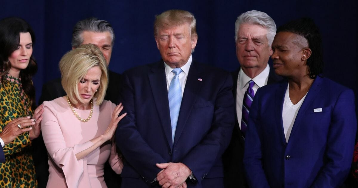 """Faith leaders pray over President Donald Trump during an """"Evangelicals for Trump"""" campaign event held at the King Jesus International Ministry on Jan. 3, 2020, in Miami."""