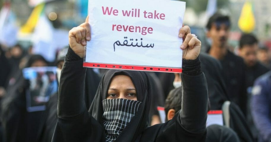 An Iraqi woman holds a placard during the funeral of Iranian military commander Qasem Soleimani in Baghdad on Jan. 4, 2020.