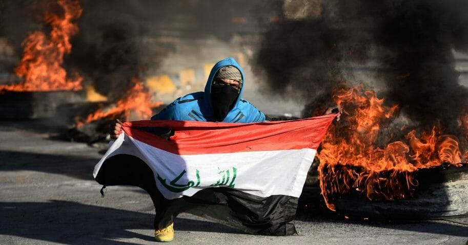 An Iraqi demonstrator carries a national flag while posing next to burning tires as angry protesters block roads in the central shrine city of Najaf on Jan. 5, 2020.