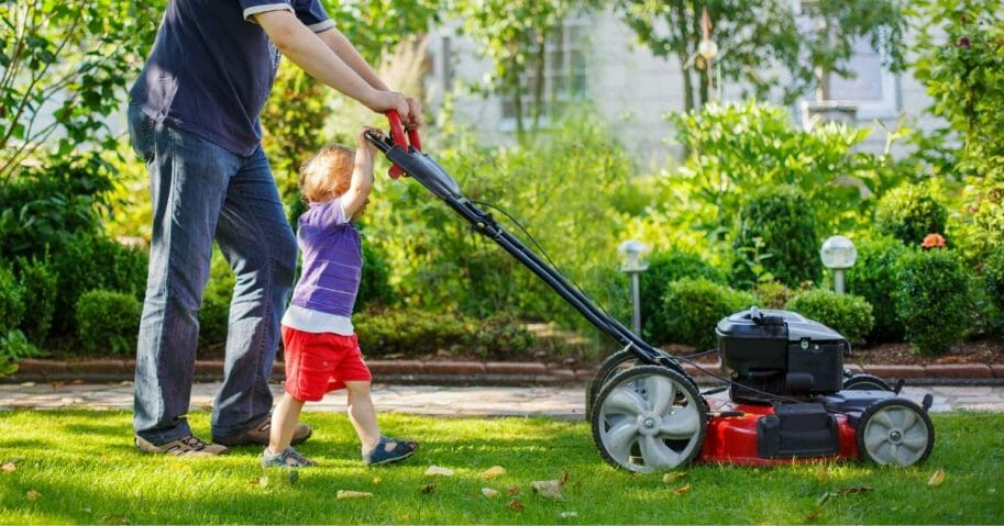Stock photo of a man and his son mowing the lawn.