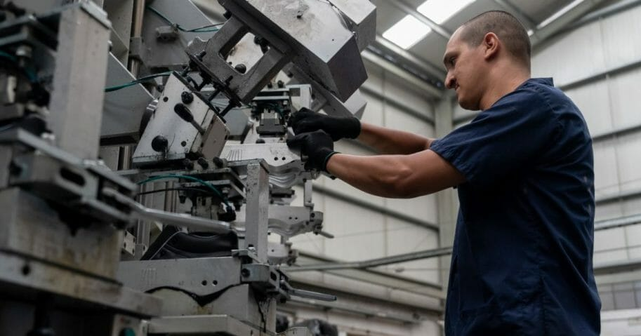 A worker operates machinery in a stock photo.