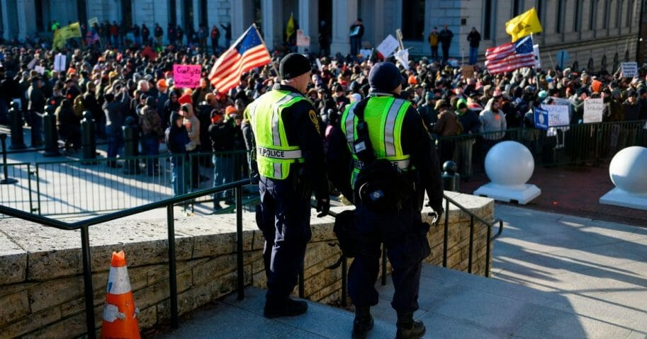 Virginia state police keep watch over a crowd gathered in front of the Virginia State Capitol in Richmond on Monday as an estimated 22,000 gun rights supporters massed near the state Capitol to demonstrate against proposed gun control laws.