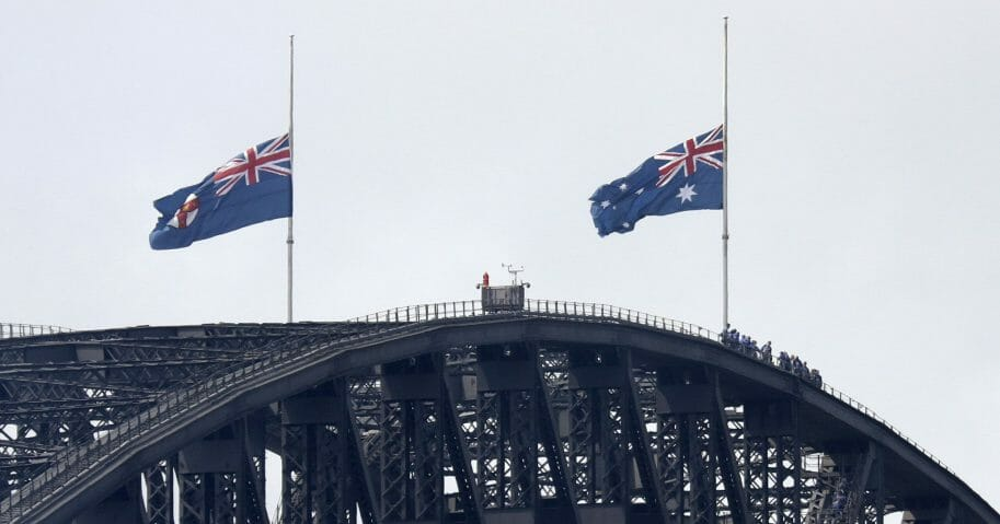 People climbing the Sydney Harbour Bridge stop under flags flying at half-mast as mark of mourning and respect in Sydney, Australia, on Jan. 24, 2020, for three U.S. crew members of an aerial water tanker that crashed while battling wildfires in Australia.