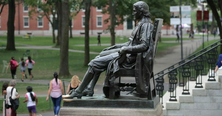 In this Aug. 13, 2019, file photo, the statue of John Harvard sits in Harvard Yard at Harvard University in Cambridge, Massachusetts.