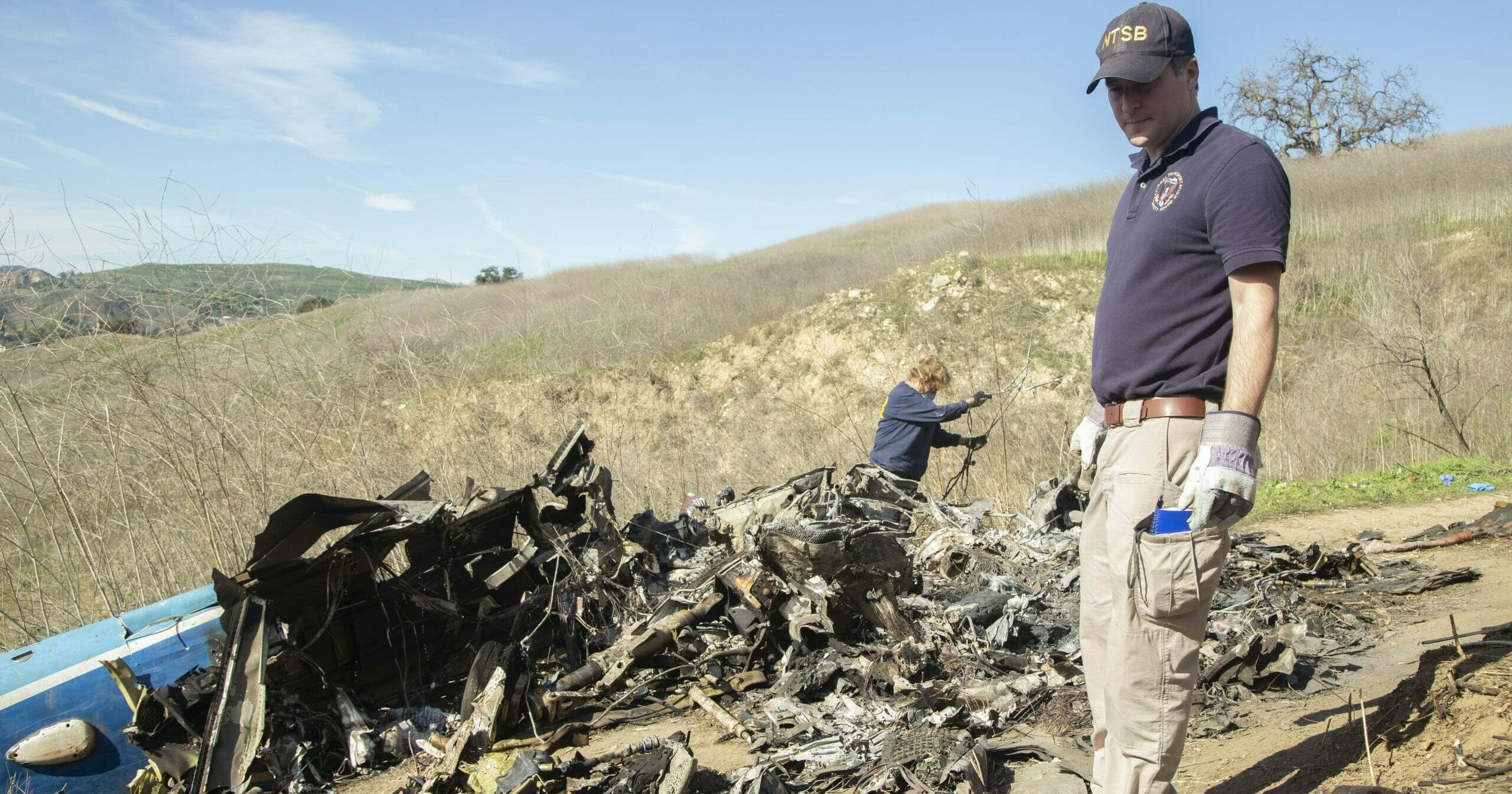In this image taken Jan. 27, 2020, and provided by the National Transportation Safety Board, NTSB investigators Adam Huray, right, and Carol Hogan examine wreckage as part of the NTSB's investigation of a helicopter crash near Calabasas, California. The Jan. 26 crash killed former NBA basketball player Kobe Bryant, his 13-year-old daughter, Gianna, and seven others.