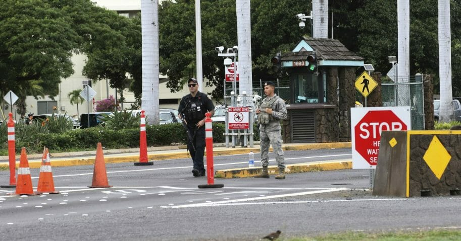 In this Dec. 4, 2019, file photo, security guards stand outside the main gate at Joint Base Pearl Harbor-Hickam in Hawaii. A live mortar round was found in a vehicle late Tuesday at a gate to the sprawling Pearl Harbor military base, shutting down the base for hours and leading three people to be taken into custody, military officials said Wednesday.