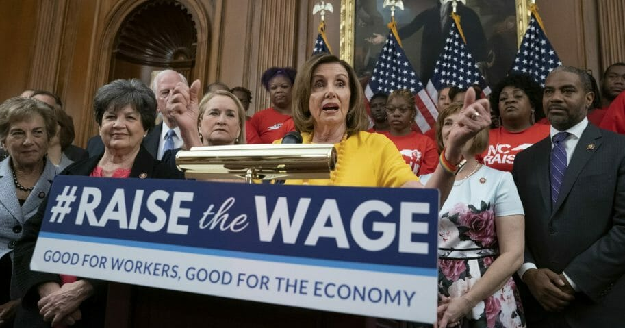 In this July 18, 2019, file photo, Speaker of the House Nancy Pelosi joins fellow Democrats and activists seeking better pay as the House approved legislation to raise the federal minimum wage for the first time in a decade at the Capitol in Washington, D.C. As of Jan. 1, 2020, there are higher minimum wages in a quarter of the states, and new federal overtime rules.