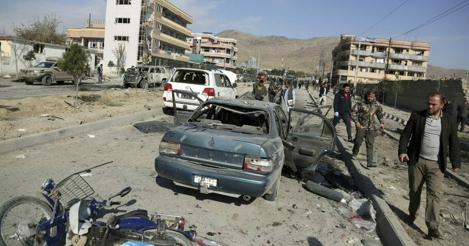 In this Nov. 13, 2019, file photo, Afghan security personnel gather at the site of a car bomb attack in Kabul, Afghanistan.