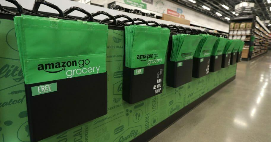 In this Feb. 21, 2020 photo, reusable shopping bags are displayed inside an Amazon Go Grocery store set to open soon in Seattle's Capitol Hill neighborhood.