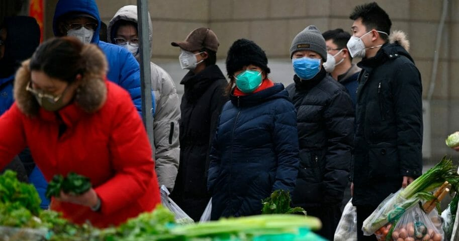 People wearing masks line up to pay for vegetables at an open market as snow falls in Beijing on Feb. 2, 2020.