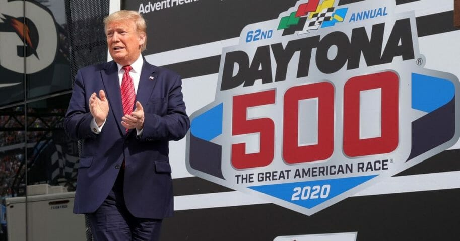 President Donald Trump speaks as first lady Melania Trump looks on from Victory Lane prior to the NASCAR Cup Series 62nd Annual Daytona 500 at Daytona International Speedway on Feb. 16, 2020, in Daytona Beach, Florida.