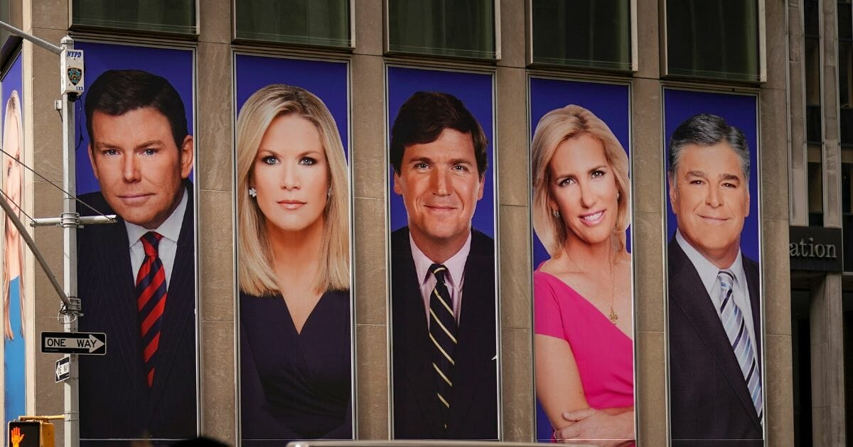 Traffic on Sixth Avenue passes by advertisements featuring Fox News personalities, including Bret Baier, Martha MacCallum, Tucker Carlson, Laura Ingraham and Sean Hannity, adorn the front of the News Corporation building on March 13, 2019, in New York City.