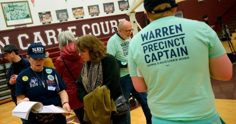 Precinct members for Democratic presidential candidate Sen. Elizabeth Warren try to sway an undecided voter during caucusing at Abraham Lincoln High School in Des Moines, Iowa, on Feb. 3, 2020.