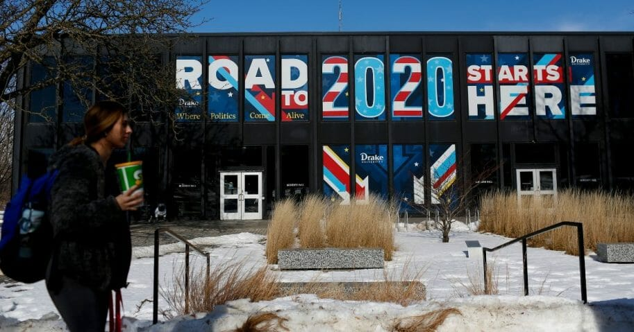 "A woman walks past a sign displayed on a building at Drake University in Des Moines, Iowa, that reads ""Road To 2020 Starts Here"" on Feb. 2, 2020, the day before the Iowa caucuses."