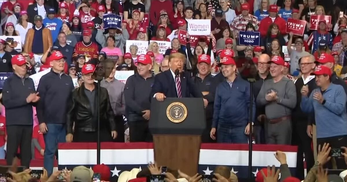 """Members of the 1980 """"Miracle on Ice"""" U.S. hockey team appear on stage with President Donald Trump at a rally in Las Vegas."""