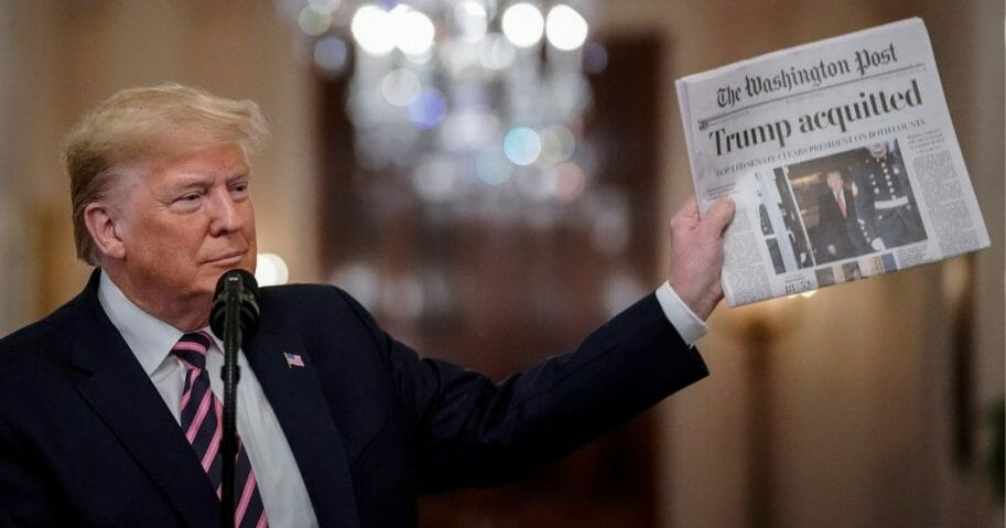 President Donald Trump holds a copy of The Washington Post as he speaks in the East Room of the White House on Feb. 6, 2020.