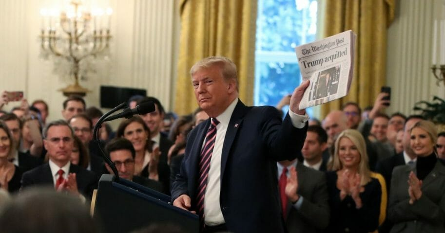 President Donald Trump holds up a newspaper as he speaks one day after the Senate acquitted him on two articles of impeachment in the East Room of the White House on Feb. 6, 2020 in Washington, D.C.