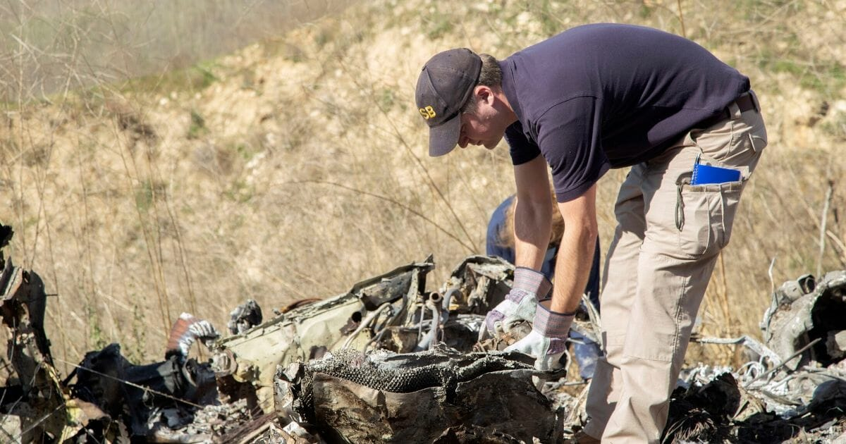 A National Transportation Safety Board investigator goes through the wreckage of the helicopter crash that killed NBA star Kobe Bryant, his daughter and seven others in Southern California on Jan. 26.