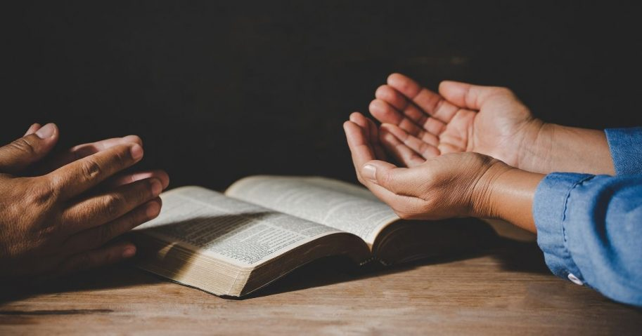 Stock image of people praying with a Bible.