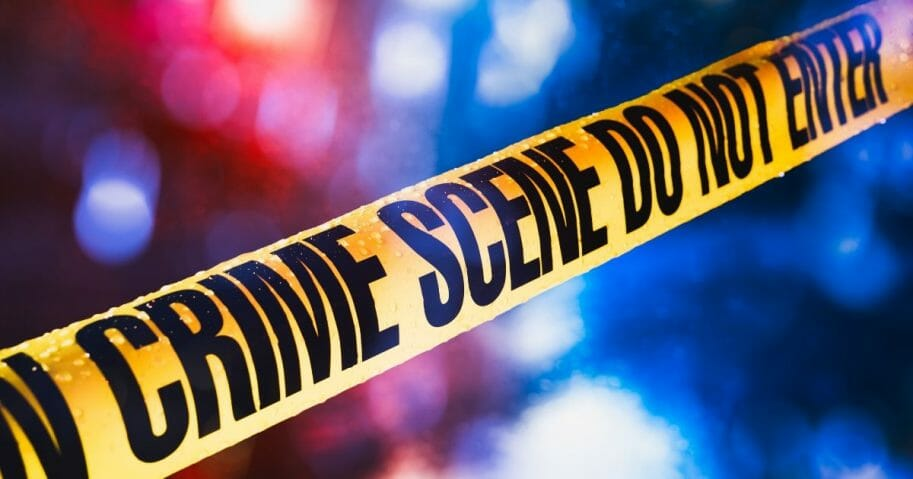 Stock image of police tape at a crime scene.