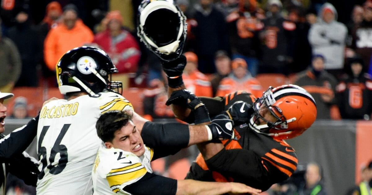 Cleveland Browns defensive end Myles Garrett swings a helmet at Pittsburgh Steelers quarterback Mason Rudolph during the second half of a Nov. 14 game at FirstEnergy Stadium in Cleveland, Ohio.