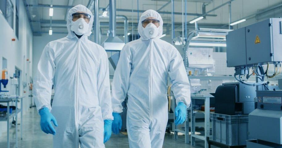 Stock image of two people in hazmat suits walking through a laboratory.