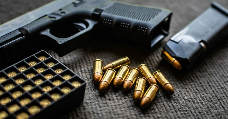 Stock image of a pistol and bullets on a gray cloth.