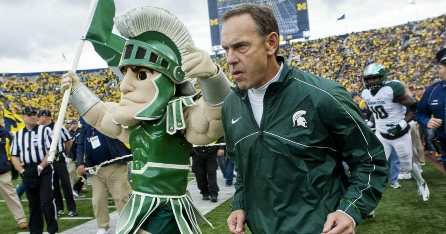 Michigan State head coach Mark Dantonio, right, runs out on to the Michigan Stadium field alongside the school mascot, Sparty, before an Oct. 20, 2012, game against Michigan in Ann Arbor.