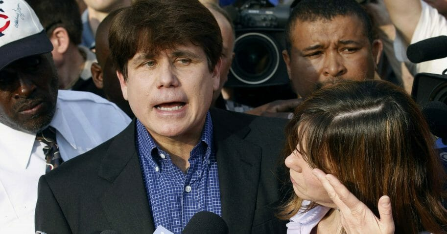 Former Illinois Gov. Rod Blagojevich speaks to the media outside his home in Chicago on March 14, 2012, as his wife, Patti, wipes away tears a day before he reported to prison after his conviction on corruption charges.