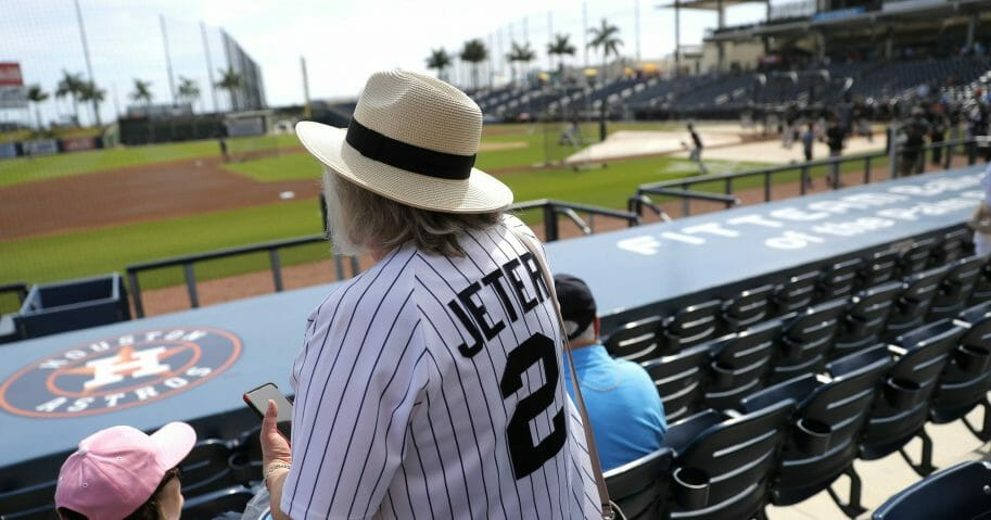 A woman wearing a Derek Jeter jersey settles into her seat prior to a spring training game between the New York Yankees and the Washington Nationals on March 12, 2020, in West Palm Beach, Florida.