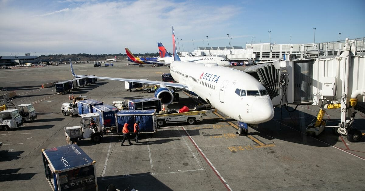 A ground crew prepares to unload luggage from an arriving Delta Airlines flight at the Seattle-Tacoma International Airport on March 15, 2020, in Seattle, Washington.