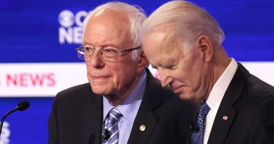 Democratic presidential candidates Sen. Bernie Sanders of Vermont and former Vice President Joe Biden speak during a break in the primary debate at the Charleston Gaillard Center in Charleston, South Carolina, on Feb. 25, 2020.