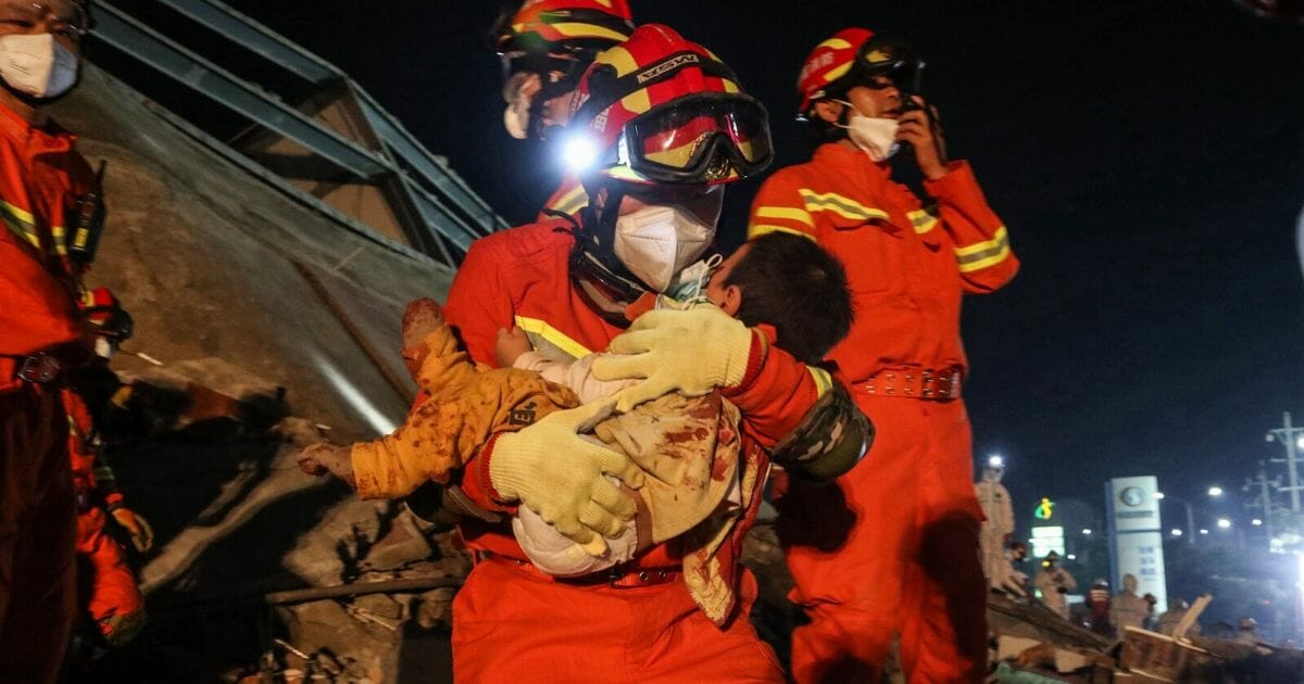A boy is rescued from the rubble of a collapsed hotel in Quanzhou, in China's eastern Fujian province early on March 8, 2020.