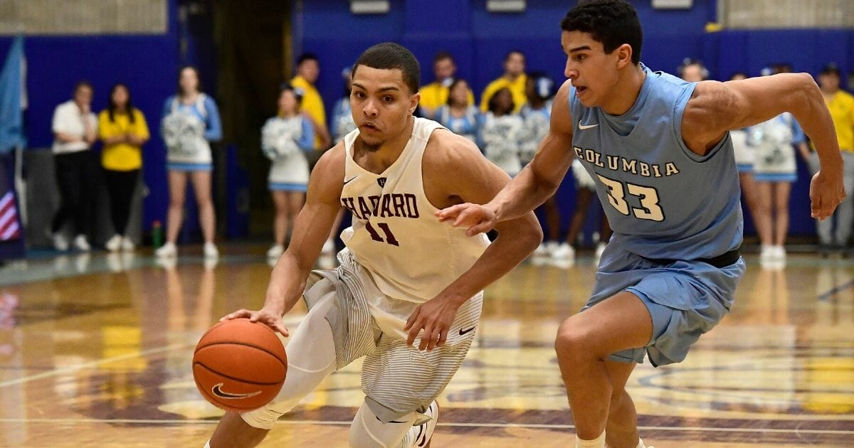 Bryce Aiken #11 of the Harvard Crimson is defended by Tai Bibbs #33 of the Columbia Lions at Frances S. Levien Gymnasium on March 9, 2019, in New York City.